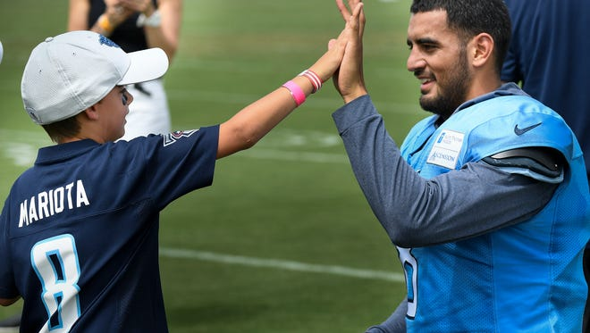 Titans fan Rowan Marko, 7, high-fives Titans quarterback Marcus Mariota (8) after a joint practice Wednesday with the Buccaneers at Saint Thomas Sports Park.