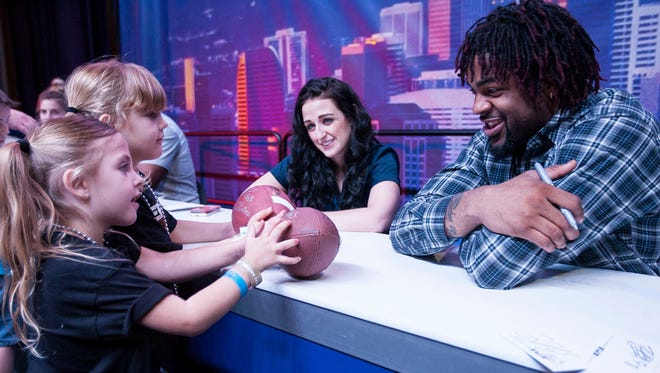 Kellie (left) and Kaydence Coleman get an autograph from New York Giants defensive end Damontre Moore at the NFL Experience at the Phoenix Convention Center on Jan. 25, 2015.