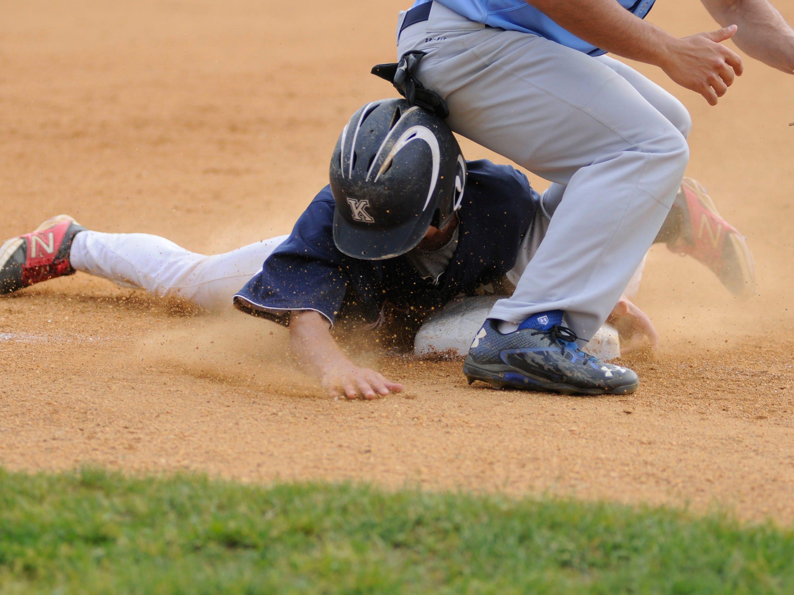 Roy C. Ketcham High School's Matt Lynch slides into third base while John Jay High School's Peter DiMeglio waits for the throw.
