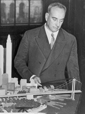 Urban planner Robert Moses with a model of his proposed Battery Bridge.