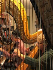 Harp instructor Pam Weest-Carrasco (right) practices