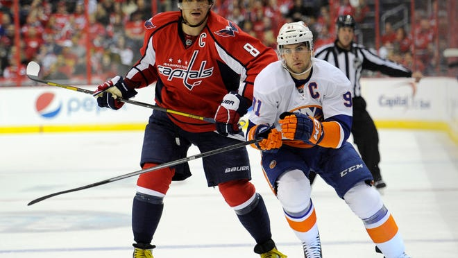 FILE - In this Nov. 5, 2013, file photo,Washington Capitals right wing Alex Ovechkin (8), of Russia, skates next to New York Islanders center John Tavares (91) during the first period of an NHL hockey game in Washington. Sidney Crosby and the Pittsburgh Penguins are hitting Broadway to face the Blueshirts for the NHL playoffs for the second straight year. Lightning GM Steve Yzerman's facing his former team in Detroit. Ottawa and Montreal face off in a cross-border rivalry. And then there's Ovechkin vs. Tavares in a full slate of compelling Eastern Conference first-round matchups. (AP Photo/Nick Wass, File)