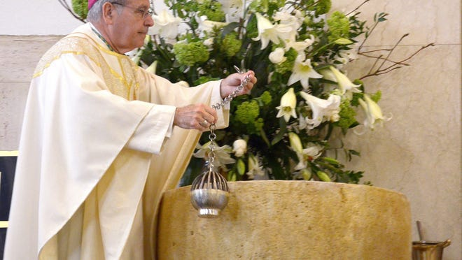 Bishop Felipe Estevez, shown blessing a Baptismal Font during a mass of celebration at the Cathedral Basilica in 2013, will ordain six men into the priesthood Saturday, June 20.