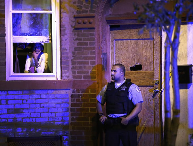 A police officer guards a home where a man was shot in the chest in the Humboldt Park neighborhood on Sept. 20 in Chicago. Thirteen people were wounded. Two are in critical condition while others were reported in serious to fair condition.