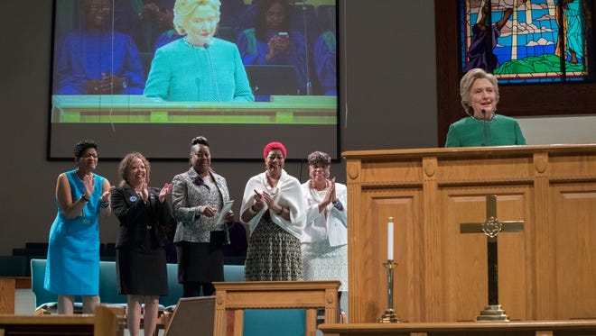 Democratic presidential candidate Hillary Clinton is joined by mothers of black men who died from gun violence, Geneva Reed-Veal, left, mother of Sandra Bland, Lucia McBath, second from left, mother of Jordan Davis, Sybrina Fulton, center, mother of Trayvon Martin, Maria Hamilton, second from right, mother of Dontre Hamilton, and Gwen Carr, mother of Eric Garner as she speaks during Sunday service at Union Baptist church, Sunday, Oct. 23, 2016, in Durham, N.C.