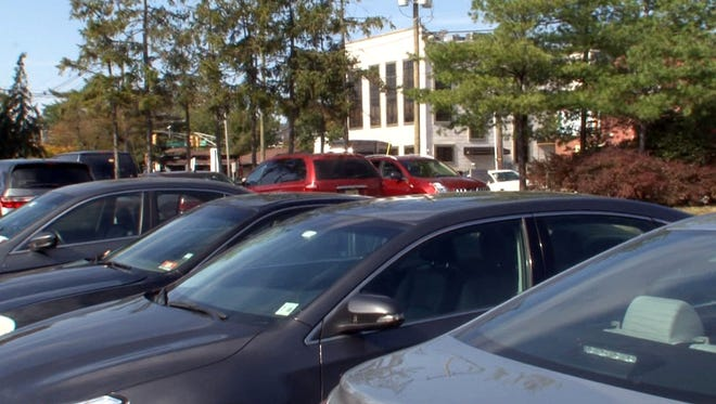 Cars that cannot find a space behind an building at 401 Madison Avenue in Lakewood (center, background) have been filling a municipal parking lot shown Tuesday, October 20, 2015.