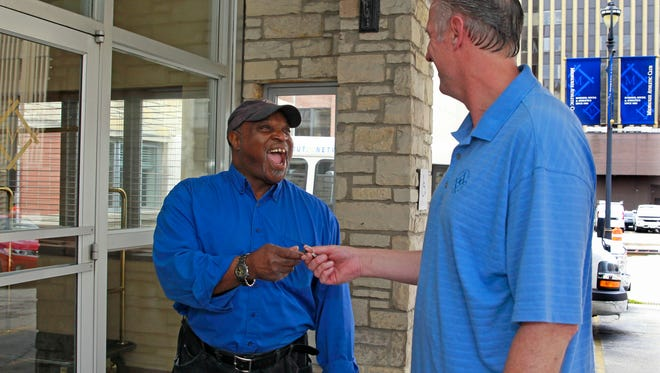 James Jackson (left), a parking valet at the Milwaukee Athletic Club for 40 years, jokingly takes the car keys of Rob Grede, a former board member at the club.