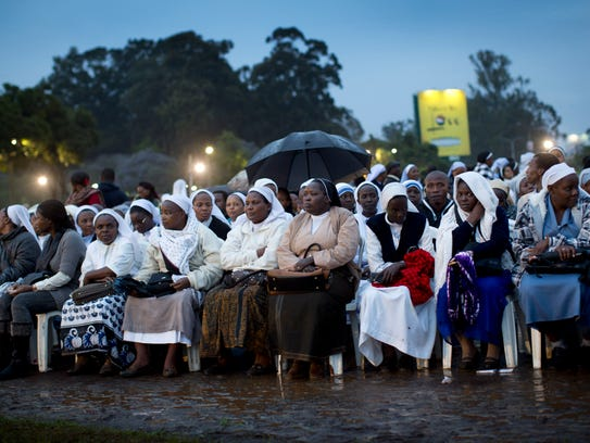 Catholic sisters wait just after dawn in the rain and