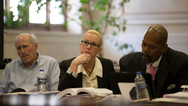 Defendant Crysta Pleatman, center, listens to testimony with her husband Dr. Stephen Pleatman, left, and attorney Clyde Bennett in the courtroom of Judge Jody Luebbers in the Hamilton County Courthouse in downtown Cincinnati on Jan. 12, 2016.
