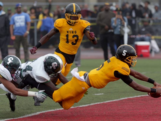 Detroit King quarterback Dequan Finn dives into the