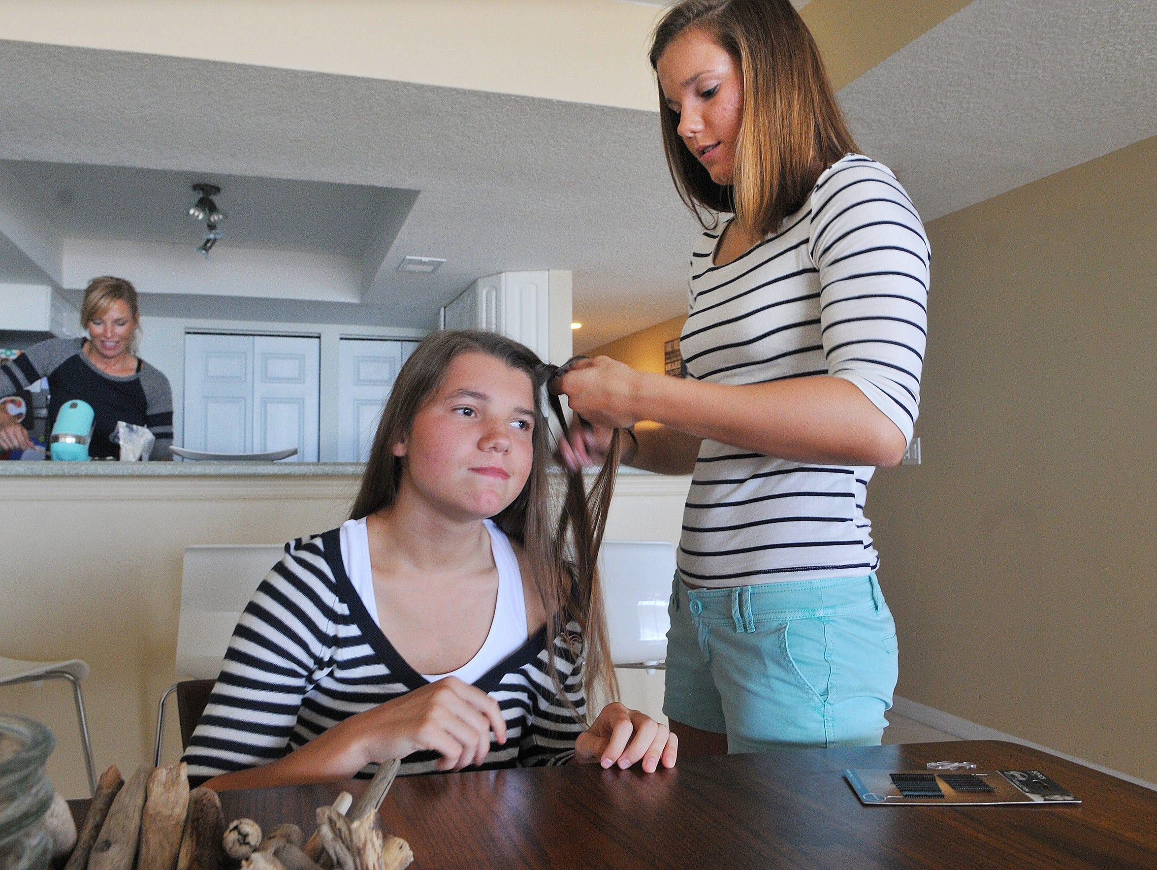 Adrianna helps braid Olivia's hair.