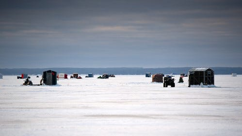 Ice fishing shelters dot the surface of a lake.