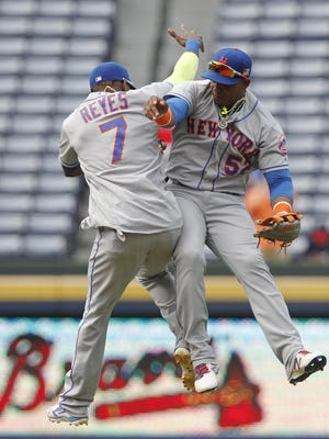 The New York Mets' Yoenis Cespedes (52) celebrates with teammate Jose Reyes (7) after Sunday's game against the Atlanta Braves in Atlanta on Sunday, Sept. 11, 2016. The Mets defeated the Braves 10-3.
