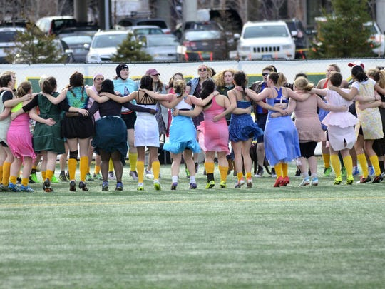 The University of Vermont women's rugby club team huddles together before the start of the prom dress game against Johnson State College on Sunday, April 9, 2017.