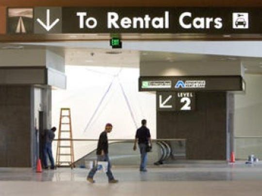 2006: One-stop rental car service- Sky Harbor's Rental Car Center opens, consolidating rental-car outlets in one space. The airport also completes renovations to Terminal 4, expanding its restaurant and shopping options, and brings free Wi-Fi inside all three of its terminals. | Workers put the final touches on the new Phoenix airport Rental Car Center in 2006.