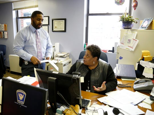 Cincinnati police detective Marcus McNeil talks with homicide victims practitioner Karen Rumsey about a call he received from a victim involved in a case at their office in downtown Cincinnati on Monday, March 7, 2016.