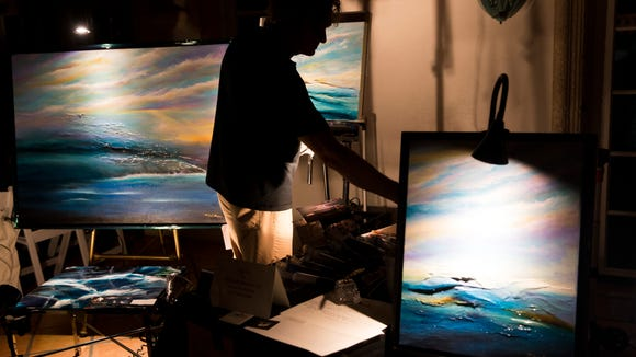 """Artist Michael Monroe hosts a live painting session for passerby during """"Dream or Reality"""", an artistic monthly community night hosted at Shangri-La Springs Wednesday, Jan. 10, 2018 in downtown Bonita Springs."""