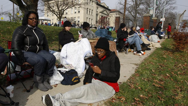 Parents have been camping out for years to get into Cincinnati Public magnet elementaries. Shown, Marsha Lane of Evanston, front, checks a text message as she and her friend April Gordon of Norwood camp out in front of the Clifton-Fairview German Language School in Clifton in 2009.