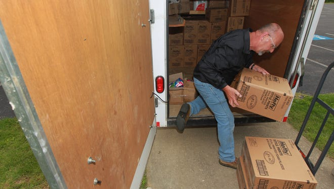 Ernie Boggs unloads a donation from Dollar General at Pleasant Grove United Methodist Church on Tuesday.
