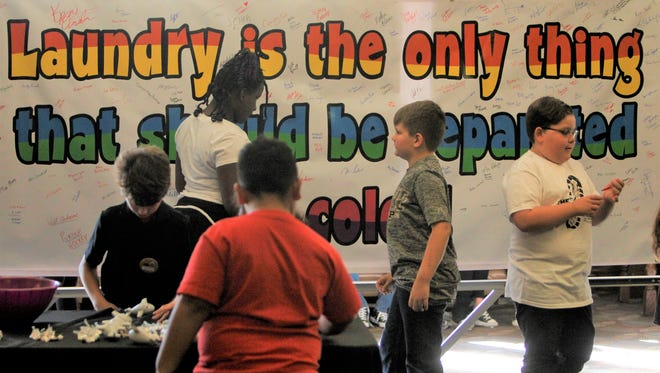 Fourth-graders from Amelia Earhart Elementary School spent Tuesday morning encouraging people to sign their banner promoting diversity.