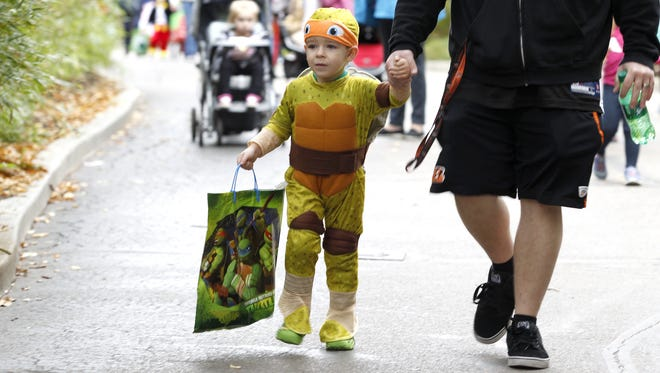 Dressed as a Teenage Mutant Ninja Turtle, Max Barker, 3, walks with his father, Brandon Barker of Williamstown, during HallZOOween at the Cincinnati Zoo & Botanical Garden on October 18.