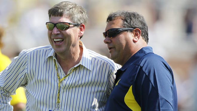 Michigan AD Dave Brandon, left, talks with football coach Brady Hoke as the team warms up Sept. 3, 2011.