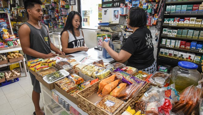 Business founder Estrella Buhain, right, rings up a purchase for siblings, Peter Meno, 17, left, and Gea Meno, 18, inside the John B's Mart and Water Station in Dededo on Saturday, Aug. 19, 2017.