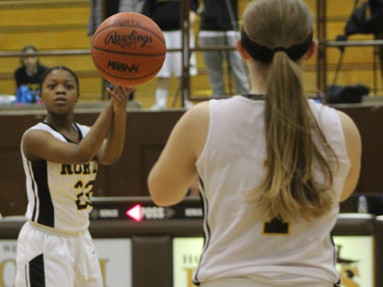 North Farmington senior guard Khyra King-ealy (23) passes off to teammate Molly Simpson (1) Thursday at home against Southfield A&T.