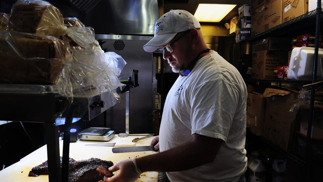 In 2014, Pat Martin cuts brisket at his Belmont Boulevard location of Martin's Bar-B-Que