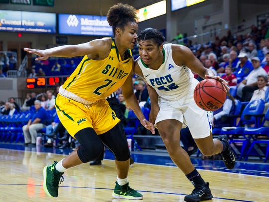 Florida Gulf Coast University freshman, Tytionia Adderly, drives towards the net as Siena College junior, Kollyns Scarbrough, plays defense during the game against Siena College on Friday, December 9, 2016 at Alico Arena in Estero, Fla.