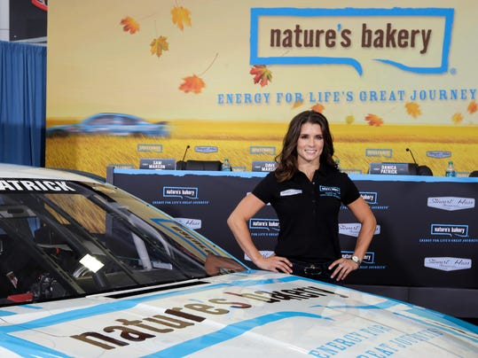 FILE - In this Aug. 18, 2015, file photo, Danica Patrick poses by her new race car during a news conference to announce a new sponsorship for her NASCAR auto racing team at Stewart-Haas Racing's headquarters in Kannapolis, N.C. One of Danica Patrick's sponsors has stepped up to fill a sudden funding void created when Stewart-Haas Racing sued her primary backer for $31 million in a breach of contract suit. Aspen Dental said Tuesday, Feb. 14, 2017,  it will be the lead sponsor for Patrick and debut on her car in the Feb. 26 season-opening Daytona 500. Patrick and SHR were left with 20-some races to fill less than two weeks before teams report to Daytona International Speedway because of a nasty split between the team and primary sponsor Nature's Bakery.(AP Photo/Chuck Burton, File)