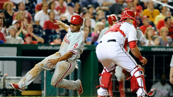 Philadelphia Phillies center fielder Ben Revere (2) slides safely home as Washington Nationals catcher Wilson Ramos (40) looks on during the eighth inning Thursday at Nationals Park. Credit: Brad Mills-USA TODAY Sports