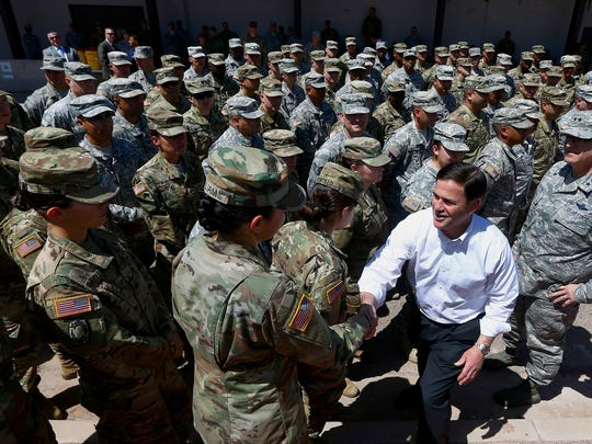 Arizona's Republican Gov. Doug Ducey, front right, meets with Arizona National Guard soldiers prior to their deployment to the Mexico border at the Papago Park Military Reservation on Monday in Phoenix.