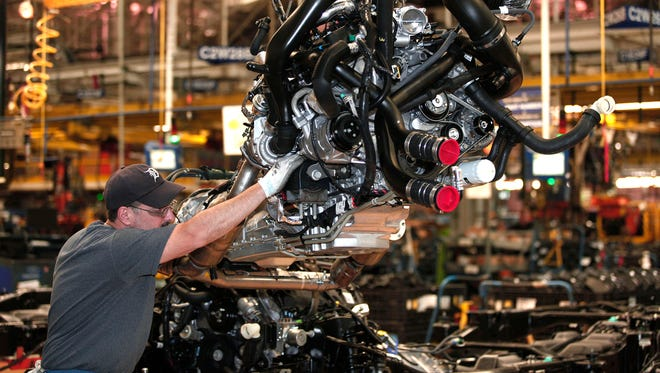 Workers install a Ford EcoBoost engine into a F-150 truck chassis on the assembly line at Ford's Dearborn Truck Plant.