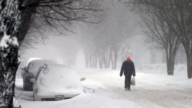 A pedestrian walks down an empty boulevard in Richmond, Va., Saturday, Jan. 23, 2016. Portions of Virginia are under a blizzard warning. A massive winter storm buried much of the U.S. East Coast in a foot or more of snow by Saturday, shutting down transit in major cities, stranding drivers on snowbound highways, knocking out power to tens of thousands of people. (AP Photo/Steve Helber)
