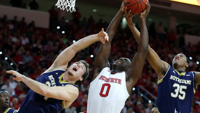 North Carolina State's Abdul-Malik Abu (0) pulls in a rebound between Notre Dame's Pat Connaughton, left, and Bonzie Colson (35) during the first half at PNC Arena in Raleigh, N.C., on Sunday, Jan. 25, 2015. (Ethan Hyman/Raleigh News & Observer/TNS)
