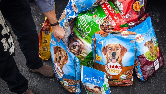 The Star Press content coach, Phil Beebe, helps load donated bags of dog and cat food during the pet food drive Thursday, Oct. 15, 2015. Locals donated more than 2,700 pounds of pet food during the event.