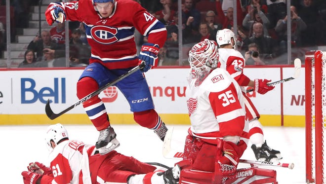 Canadiens center Byron Froese (42) jumps over Red Wings defenseman Xavier Ouellet (61) in front of goalie Jimmy Howard (35) during the third period of the Wings' 10-1 loss on Saturday, Dec. 2, 2017, in Montreal.
