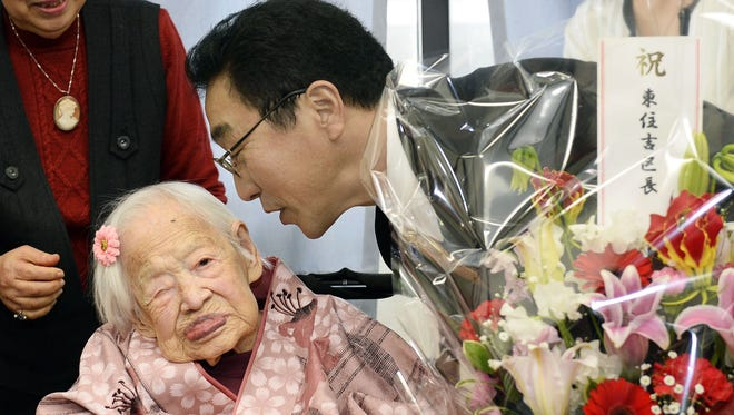 Japan's Misao Okawa, who is recognized as the world's oldest living person by Guinness World Records, is celebrated by Ward Mayor Takehiro Ogura at a nursing home in Osaka, Japan, on March 4, a day ahead of her birthday.