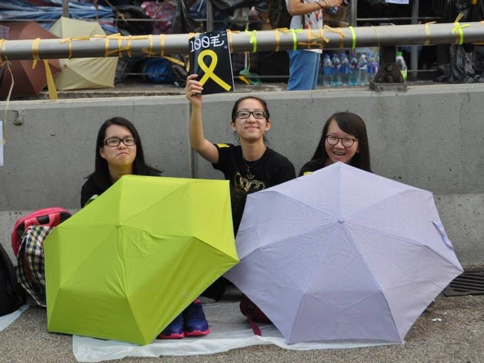 """A young woman holds a yellow ribbon, one of the many pro-democracy symbols of the peaceful """"Umbrella Revolution,"""" in Hong Kong. Contributor Becky Peterson explains: """"The protests have been dubbed the 'Umbrella Revolution,' as a large number of protesters used them to protect themselves from pepper spray and tear gas. Even pouring rain has not deterred the umbrella-clad protesters."""""""