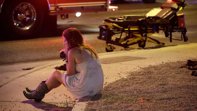A woman sits on a curb early Monday at the scene of the shooting outside of a music festival along the Las Vegas Strip.