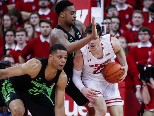 Wisconsin's Ethan Happ, right, bumps up against Michigan State's Nick Ward, center, and Miles Bridges, left, during the first half of an NCAA college basketball game Sunday, Feb. 25, 2018, in Madison, Wis. (AP Photo/Andy Manis)