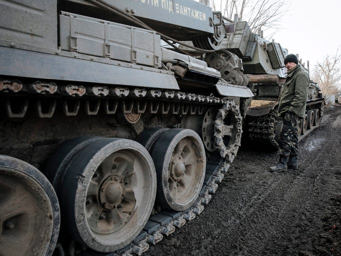 A Ukrainian serviceman stands next to tanks during