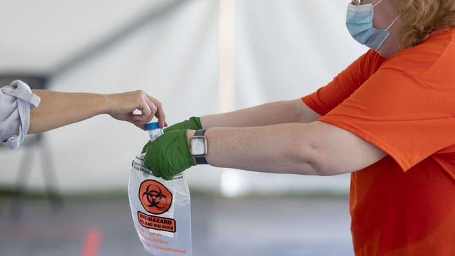 Nancy Markstahler collects a sample as COVID-19 saliva testing is conducted on July 7, 2020, in a tent outside the Alice Campbell Alumni Center on the University of Illinois campus.