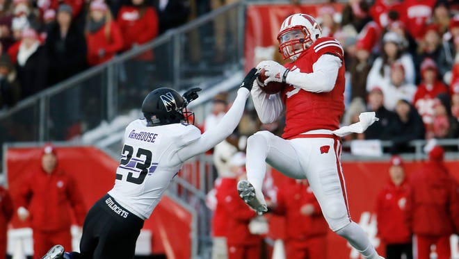 Wisconsin's Tanner McEvoy (3) catches a pass in front of Northwestern's Nick VanHoose (23) during the first half of an NCAA college football game Saturday, Nov. 21, in Madison.