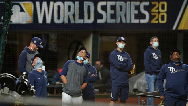 Tampa Bay Rays manager Kevin Cash, center with face mask down, watchers over a practice at Globe Life Field as the team prepares for the baseball World Series against the Los Angeles Dodgers, in Arlington, Texas, Wednesday, Oct. 14, 2020.