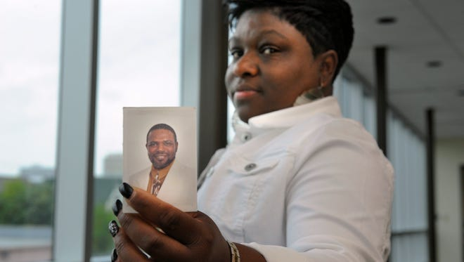 """Telesa Anderson holds a picture of her father, Elbert Thornton, who died as an inmate in 2013. Anderson thinks the state was negligent in her father's death. """"Too much happened to him for nobody not to know anything."""""""