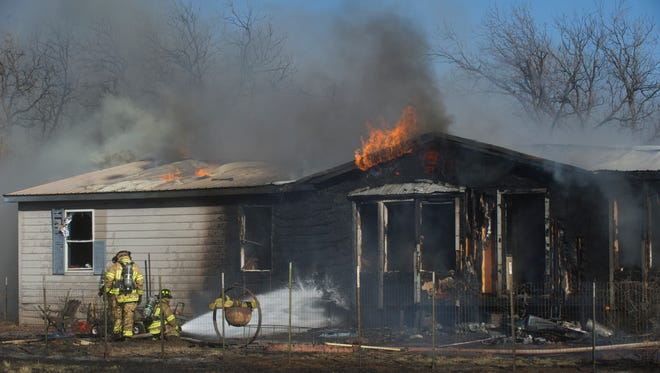 Firefighters work on a house fire in the 6100 block of Hartford Street, which started shortly after 2 p.m. Monday Five occupants were able to leave the house without sustaining any injuries.