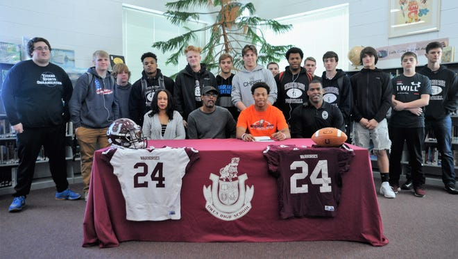 Antonio McDowell, surrounded by teammates and family members in the media center at Owen on Feb. 9, signs to play football for Carson-Newman.