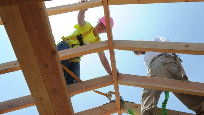Kat Meadors, left, and instructor Daniel Bell work on a tiny house being built for the Turning Point Foundation at the Girls Construction Camp.